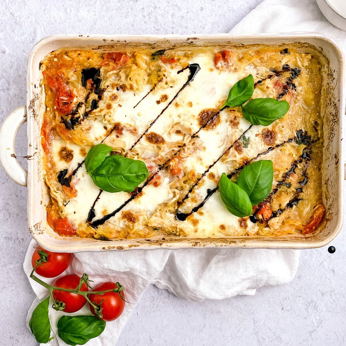 casserole dish with basil, tomatoes, and balsamic