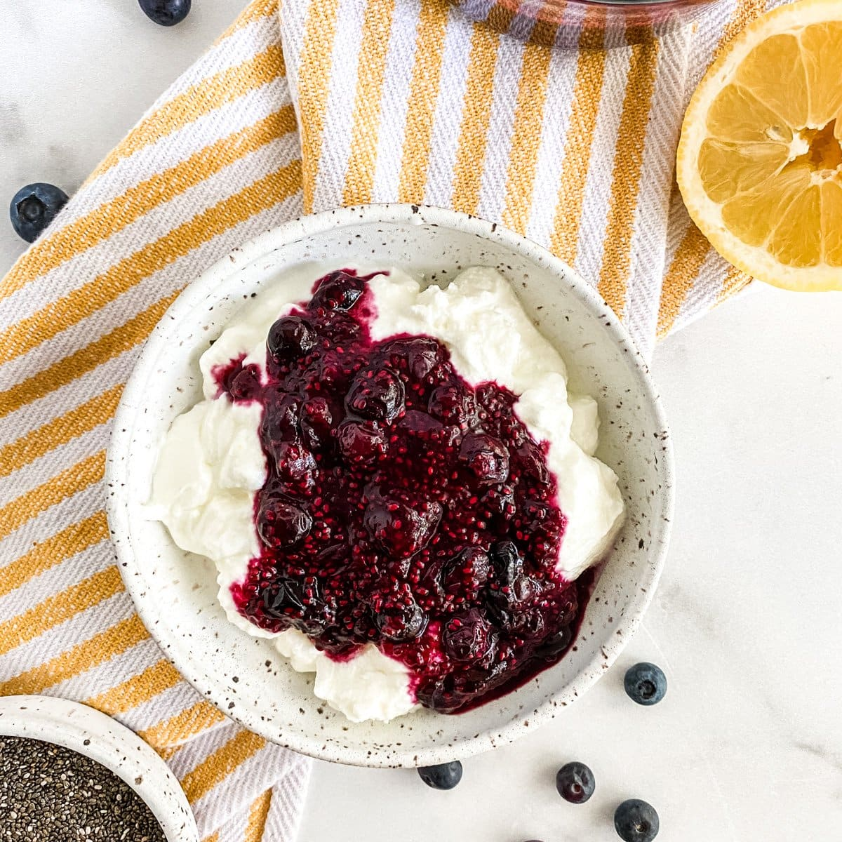 a bowl of yogurt with chia seed jam and a lemon