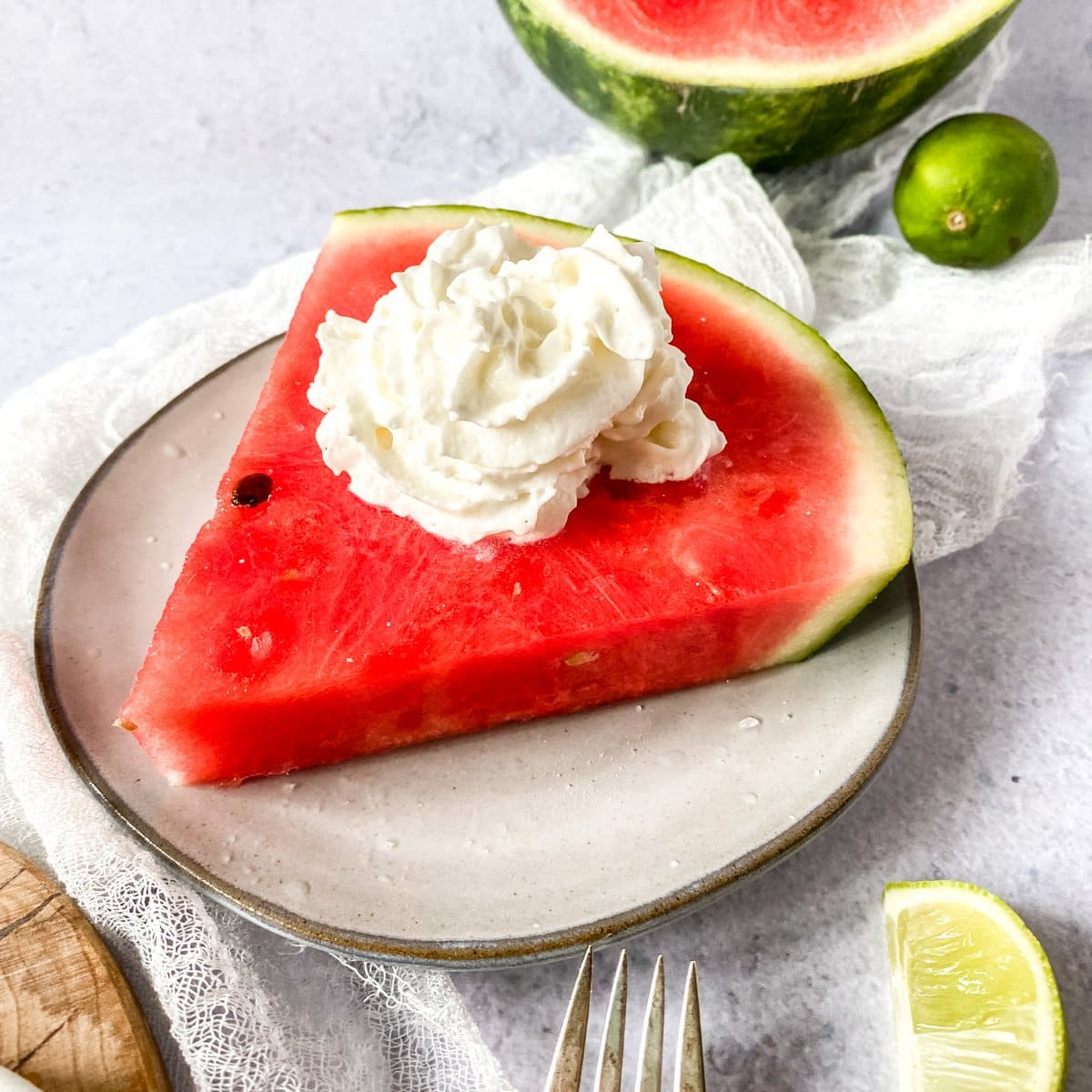 watermelon on a plate with lime and cream